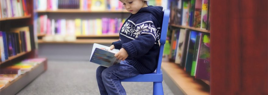 young boy reading in library