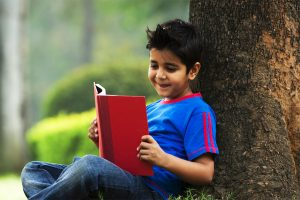 little boy reading under tree